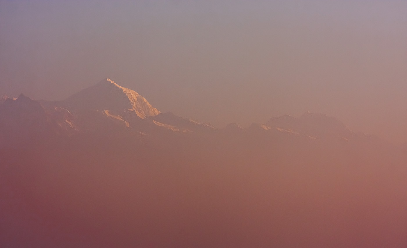 Mount Everest peaking through mystic pink morning fog